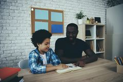 African American single father, along with son. Do homework at home. Child education concept stock images