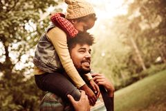 African American single father carrying daughter. stock photo