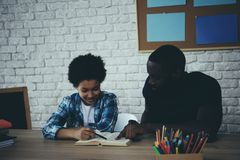 African American single father helps little son. To do homework at home. Child education concept. Fatherhood stock photos