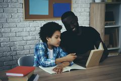 African American single father helps little son. To do homework at home. Child education concept. Fatherhood stock photo