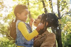 African American single mother and her daughter in meadow together having conversation. royalty free stock photography