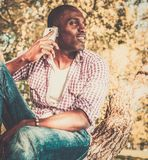 African american sitting on a tree Stock Images