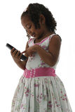 African American Small Girl in Dress with Phone. An African American girl in a floral pattern dress with a wireless cordless telephone in here hands pushing a Royalty Free Stock Photos