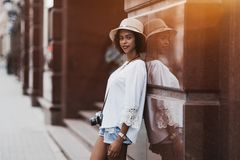 Cheerful Brazilian girl on the street with vintage photo cam stock photo
