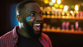 African-american soccer fan with flag on cheek cheering for team winning match. Stock footage stock video footage