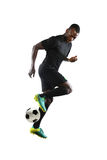 African American Soccer Player. Kicking ball isolated over white background royalty free stock image