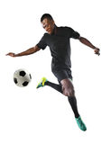 African American Soccer Player. Young African American soccer player kicking ball inside large stadium royalty free stock image