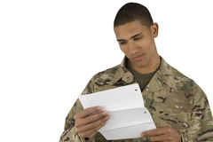 African American Soldier reads a letter. A military man smiles as he reads a letter stock photography