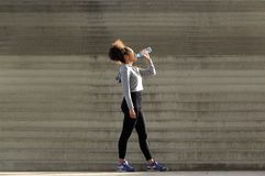 African american sports woman drinking from water bottle Stock Photos
