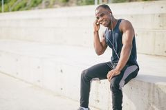 African American sportsman or jogger. black man listening to music. Shot of attractive runner with muscular athletic body dressed in black sportswear resting Stock Image
