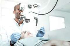 African American stomatologist exploring special equipment in his work. Dentist using machine. African American stomatologist exploring special equipment in his royalty free stock images