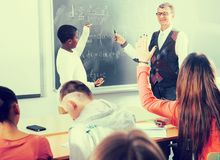 African-American student answers near blackboard at math lesson stock images