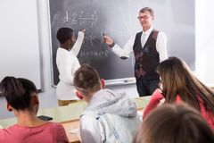 African-American student answers near blackboard at math lesson. African-American guy student answers near blackboard at math lesson Royalty Free Stock Images