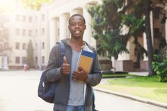 African-american student with books at university. Attractive african-american student with books at university building, showing thumb up gesture. Education Royalty Free Stock Photos