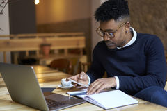 African american student of business school in dark sweater and white shirt accounting documentation for last month Stock Photography