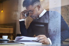 African american student of business school in dark sweater and white shirt answer on calling from operator manager. Afro american skilled hipster guy reading Royalty Free Stock Images