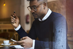 African american student of business school in dark sweater and white shirt. Cropped image of concentrated skilled architect working on developing building Stock Photo