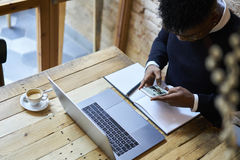 African american student of business school in dark sweater and white shirt interesting news from website using free internet Stock Image