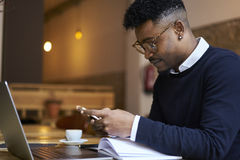 African american student of business school in dark sweater and white shirt  reading books and working at laptop. Skilled copywriter in style spectacles typing Royalty Free Stock Photo