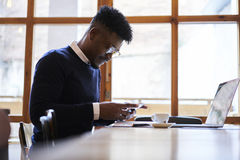 African american student of business school in dark sweater and white shirt sitting in coffee shop with modern laptop in wifi zone Stock Photos