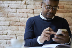 African american student of business school in dark sweater and white shirt studying remote using free wifi in coffee shop Royalty Free Stock Image