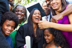 African American Student Celebrates Graduation. Happy African American Student Celebrates Graduation With Extended Family royalty free stock image