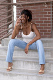 African American Student on Cell Phone on Steps Royalty Free Stock Photos