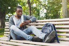 African-american student listening to music outdoors. African-american student listening to music on his smartphone outdoors, having a rest in the university Royalty Free Stock Images