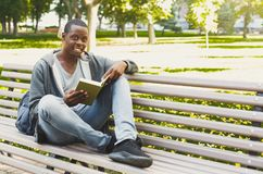 African-american student reading a book outdoors. Smiling african-american student reading a book in the park, studying and preparing for exams at the university Royalty Free Stock Images