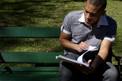 African American Student Reading Outdoors. College Student Reading Outdoors Lying in the Park Stock Photos
