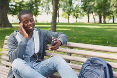 Student sitting in park and using smartphone. African-american student sitting on bench in park and listening to music on his smartphone outdoors, having rest in Stock Images