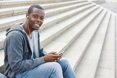 African-american student sitting on stairs and using his smartphone. Happy african-american student sitting on stairs and listening to music on his smartphone Stock Photography