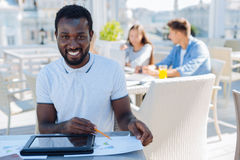 African american student studying outdoors alone. Happy to study here. Radiant guy looking into the camera and grinning broadly while sitting outdoors and Royalty Free Stock Image