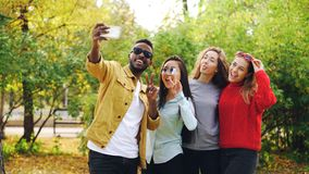 African American student is taking selfie with beautiful girls Asian and Caucasian standing in park, using smartphone royalty free stock photography