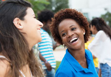 African american student talking with young caucasian woman at c. African american student talking with young caucasian women at campus of university outdoors in royalty free stock image