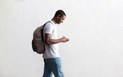 African american student walking with bag and mobile phone. Side view portrait of a african american student walking with bag and mobile phone Stock Photo
