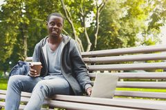 African-american student working on a laptop and drinking coffee outside. African-american student drinking coffee and working with laptop, preparing for exams Royalty Free Stock Photos
