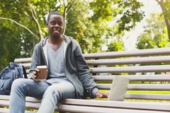 African-american student working on a laptop and drinking coffee outside. African-american student drinking coffee and working with laptop, preparing for exams Royalty Free Stock Images