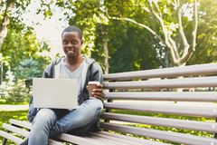 African-american student working on a laptop and drinking coffee outside. Happy black student drinking coffee and working with laptop, preparing for exams or Stock Photo