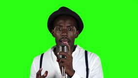 African American in a studio is singing songs into a microphone. Green screen. Slow motion. Close up stock footage