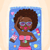 African American summer girl sunbathes on the beach. (on towel with book, glass and sunblock Stock Photo