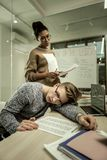 African-American teacher standing near unmotivated lazy student. Lazy student. African-American teacher wearing glasses standing near unmotivated lazy student stock image