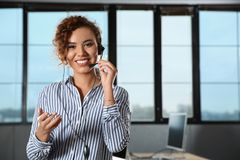 African-American technical support operator with headset in office. Space for text stock images
