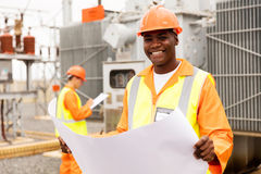 African american technician blueprint. Happy african american technician holding blueprint in substation Royalty Free Stock Image