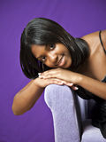 African American teen. Smiling face of a pretty African American teenager leaning on couch arm Stock Images
