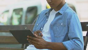 African-American teen boy scrolling tab on bench outdoors, social networks