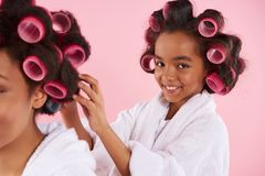 African American teen girl in curlers makes stock photo