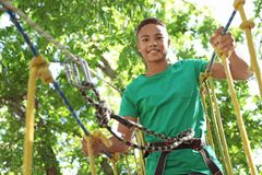 African-American teenage boy climbing in adventure park. Summer camp. Happy African-American teenage boy climbing in adventure park. Summer camp royalty free stock photos