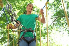 African-American teenage boy climbing in adventure park. Summer camp. Happy African-American teenage boy climbing in adventure park. Summer camp stock photography
