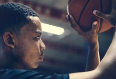 African American teenage boy concentrated on playing basketball stock photography